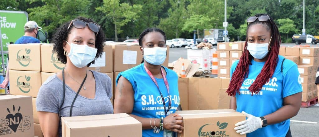 Volunteers in masks holding boxes of food
