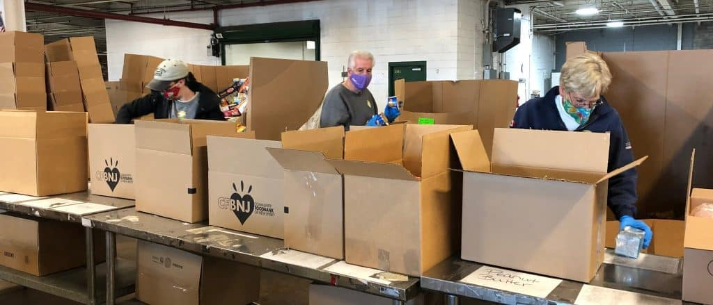 Volunteers packing boxes with food