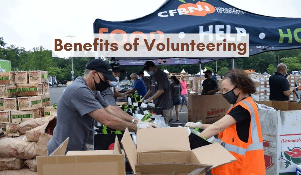 Volunteers packing food into boxes outside on a cloudy day. Volunteers are wearing masks.
